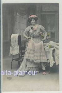 Original color photograph in postcard format depicting a woman posed amid various frilly under garments